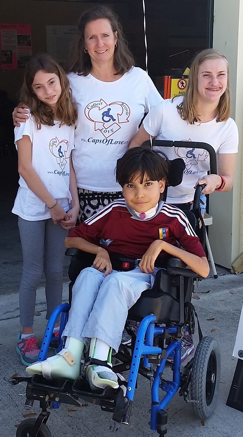woman, two young girls, and a boy in a blue wheelchair