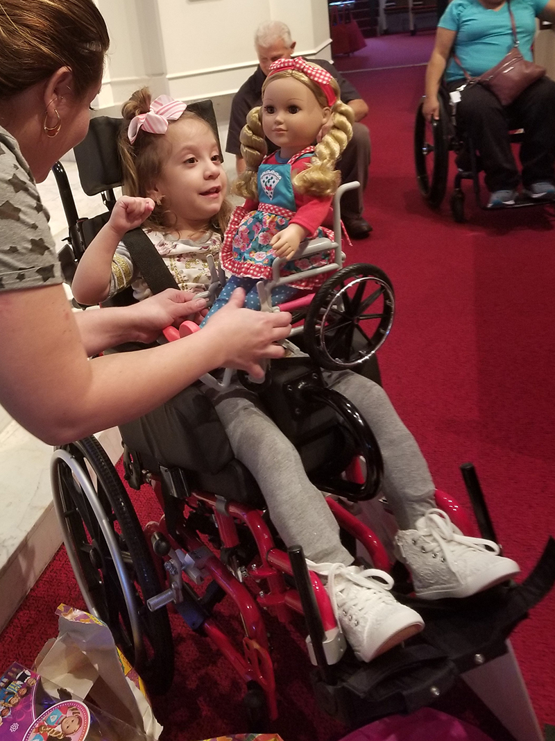young girl in a red wheelchair with a doll